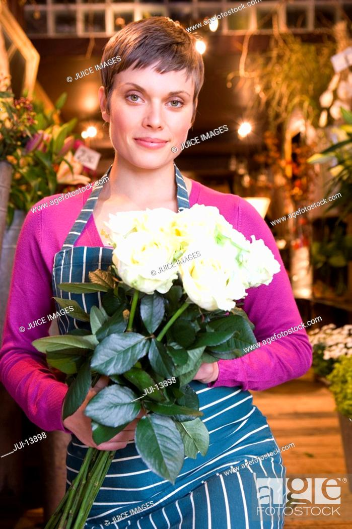 Stock Photo: Female florist with bunch of roses, smiling, portrait.