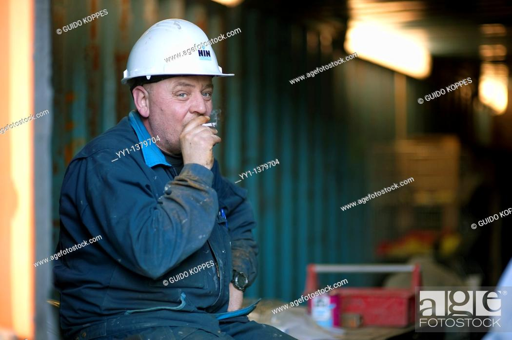 Stock Photo: A constructionworker is smoking a sigarette in a container during a break.