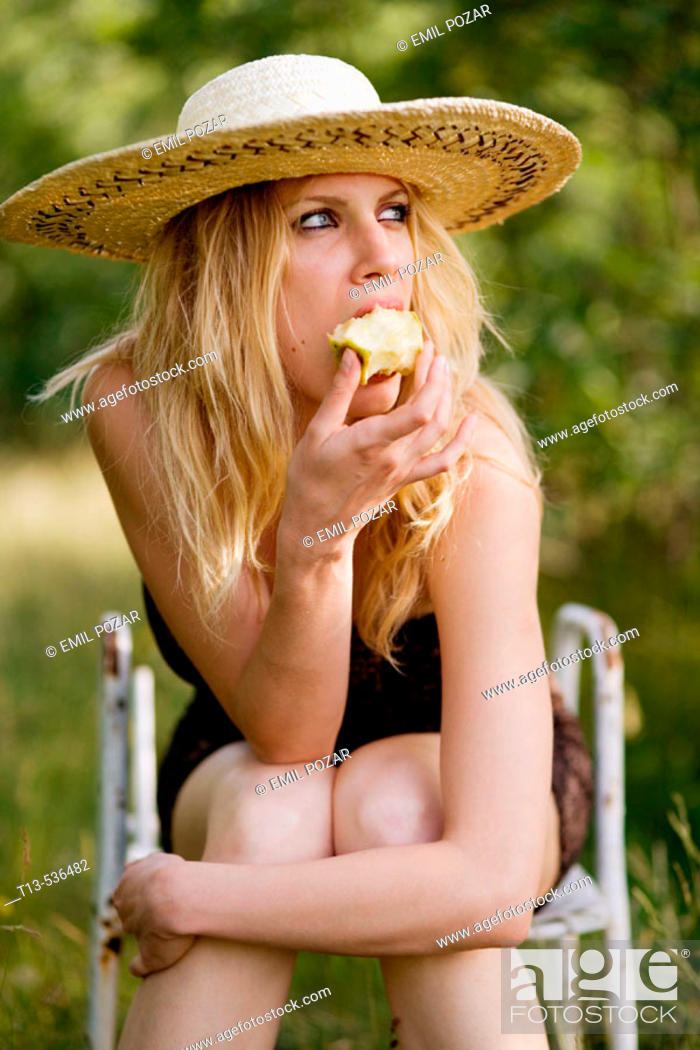 Stock Photo: Young blonde woman eating apple sitting in green grass environment.
