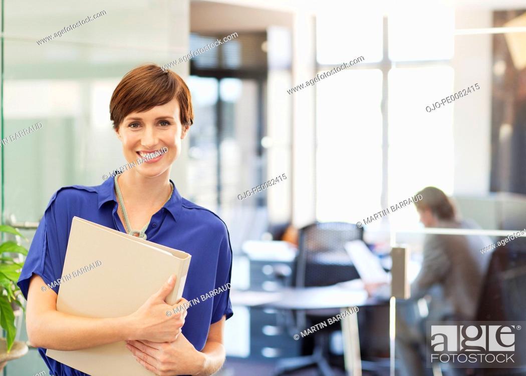 Stock Photo: Portrait of smiling businesswoman holding binder in office.