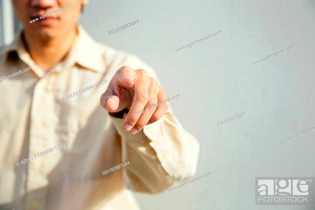 Stock Photo: Young man pointing at camera, mid section.