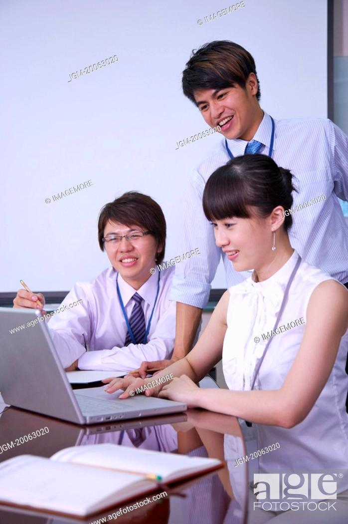 Stock Photo: Three colleagues looking at the laptop together and smiling.