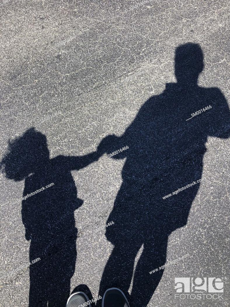 Stock Photo: Shadow of man with child in the street.