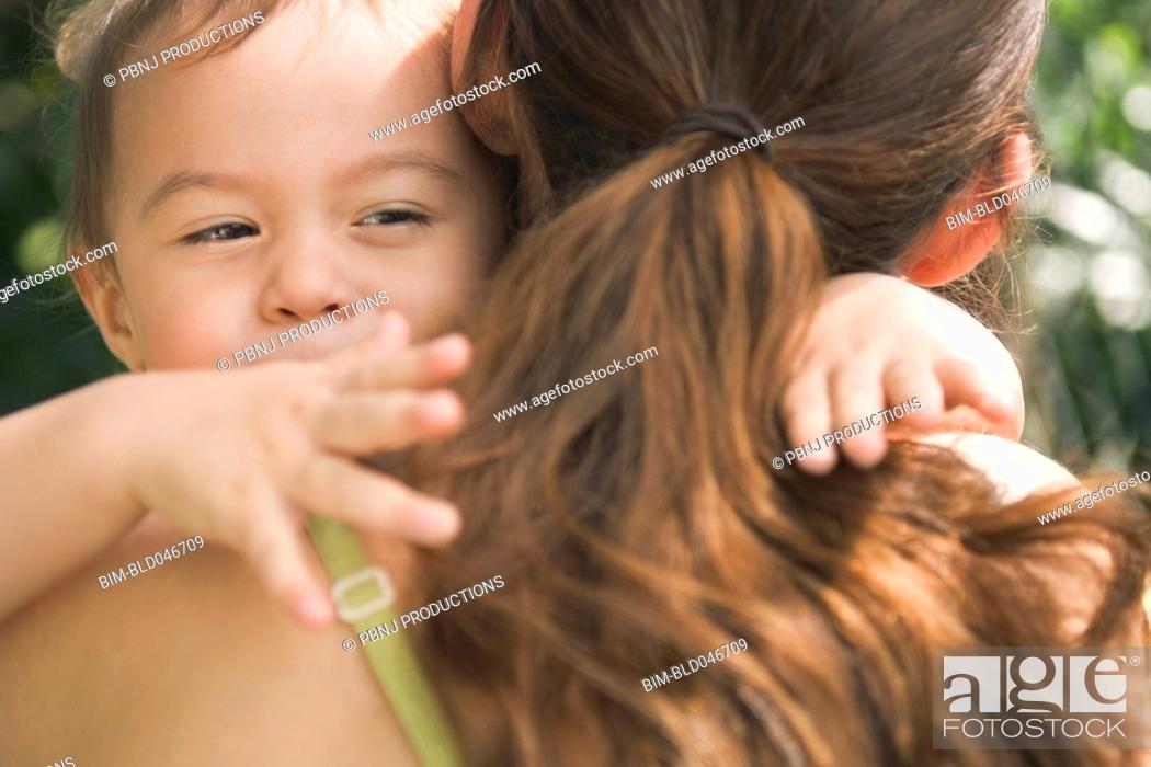 Stock Photo: Hispanic baby hugging mother.