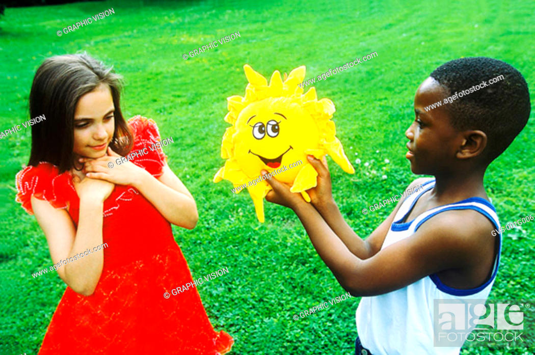 Stock Photo: Young boy giving a young girl a toy stuffed sun flower.