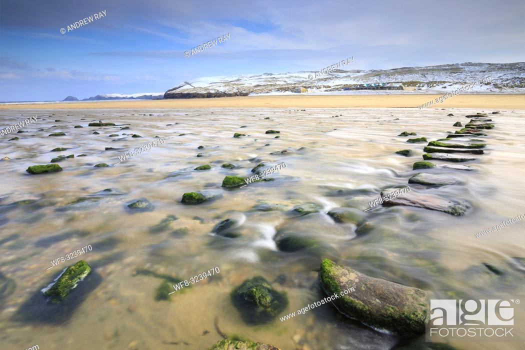Stock Photo: The stepping stones on Perranporth Beach on the North Coast of Cornwall, captured on a morning in mid March with snow covered sand dunes in the distance.