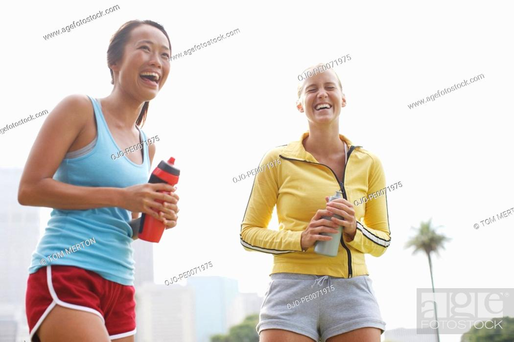 Stock Photo: Women laughing and holding water bottles.