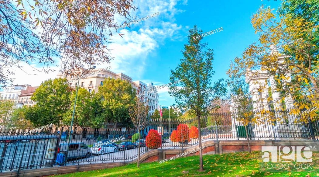 Stock Photo: Cars parked on the side of Alfonso XII Street in Madrid, Spain, as seen from inside the fence in Retiro Park. Unusually warm November day in one of the main.