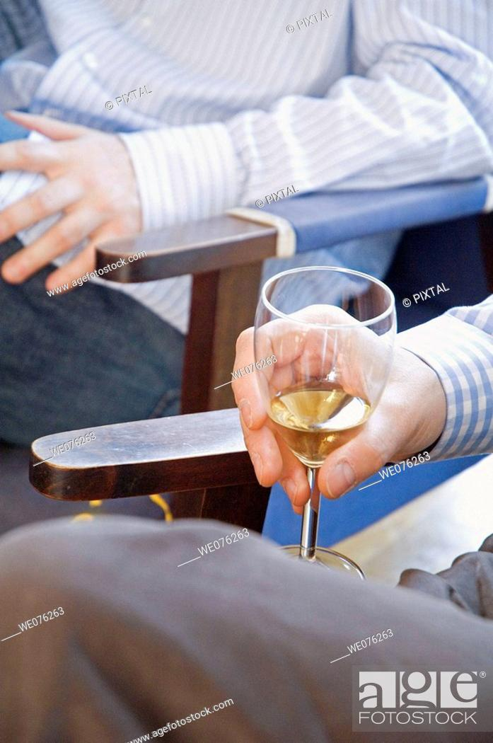 Stock Photo: Friends at a winetasting, holding white wine.
