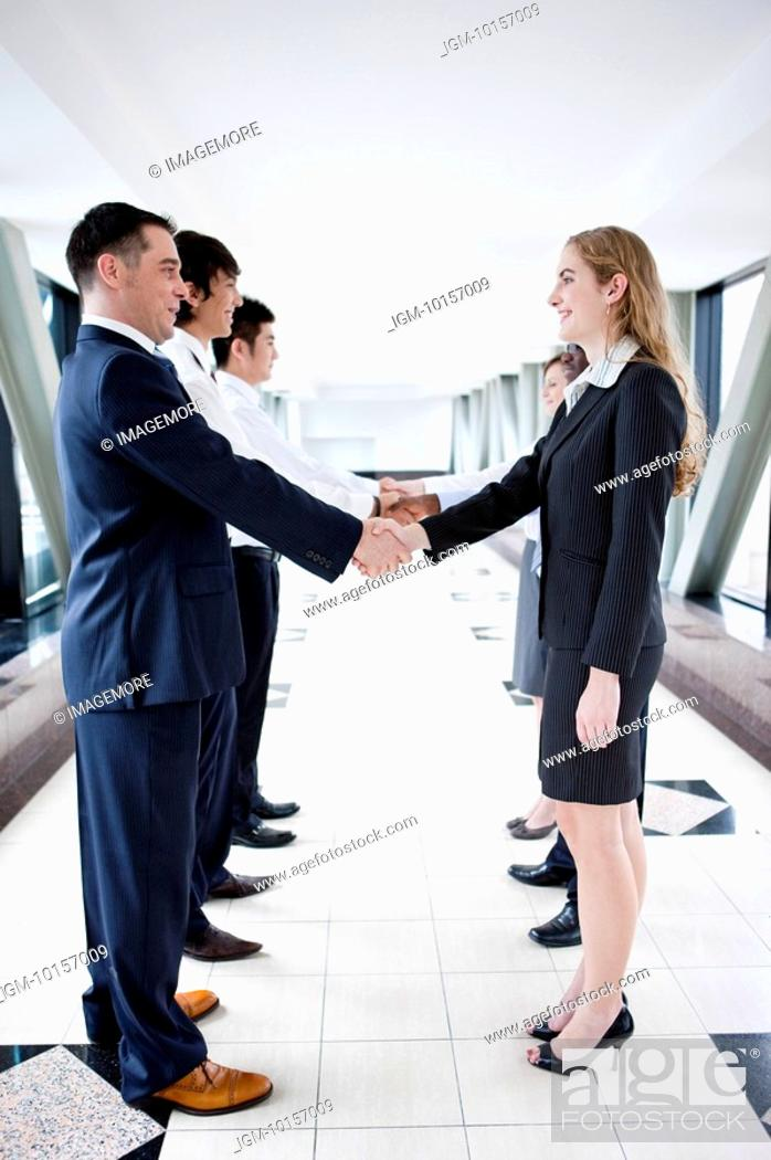Stock Photo: Business people standing in a row and shaking hands together.