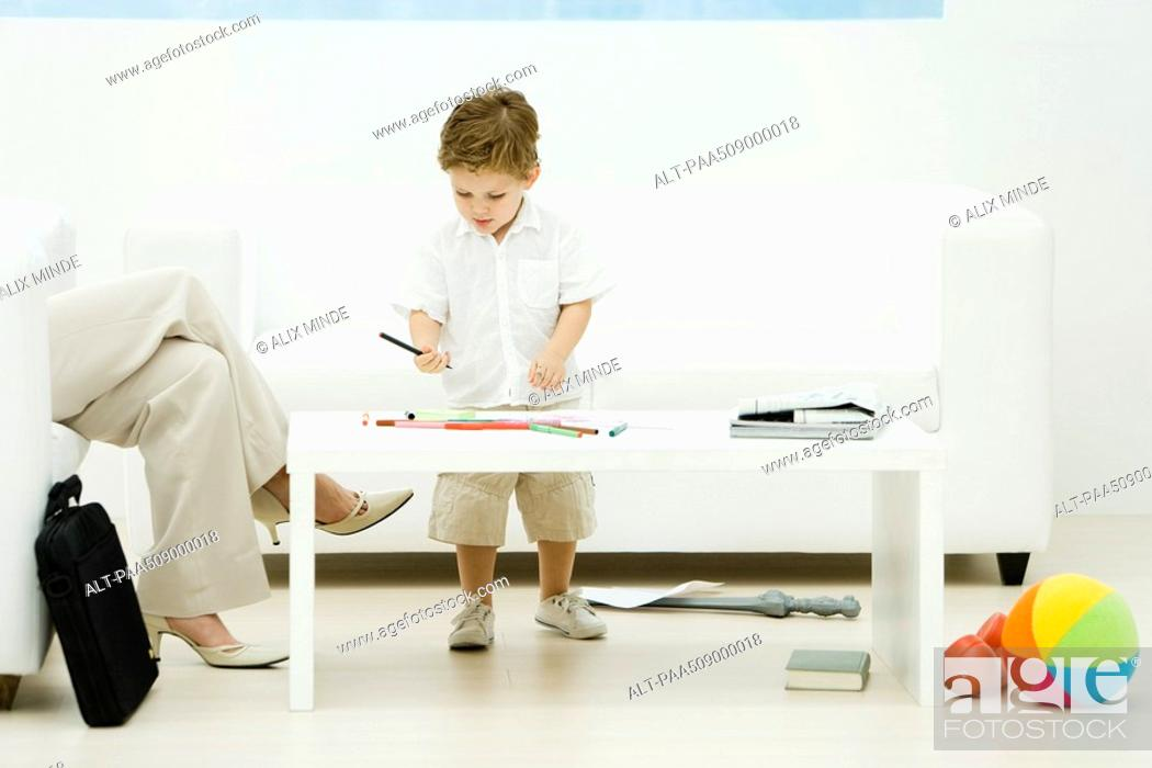 Stock Photo: Professional woman and son in waiting room, boy coloring, cropped view.