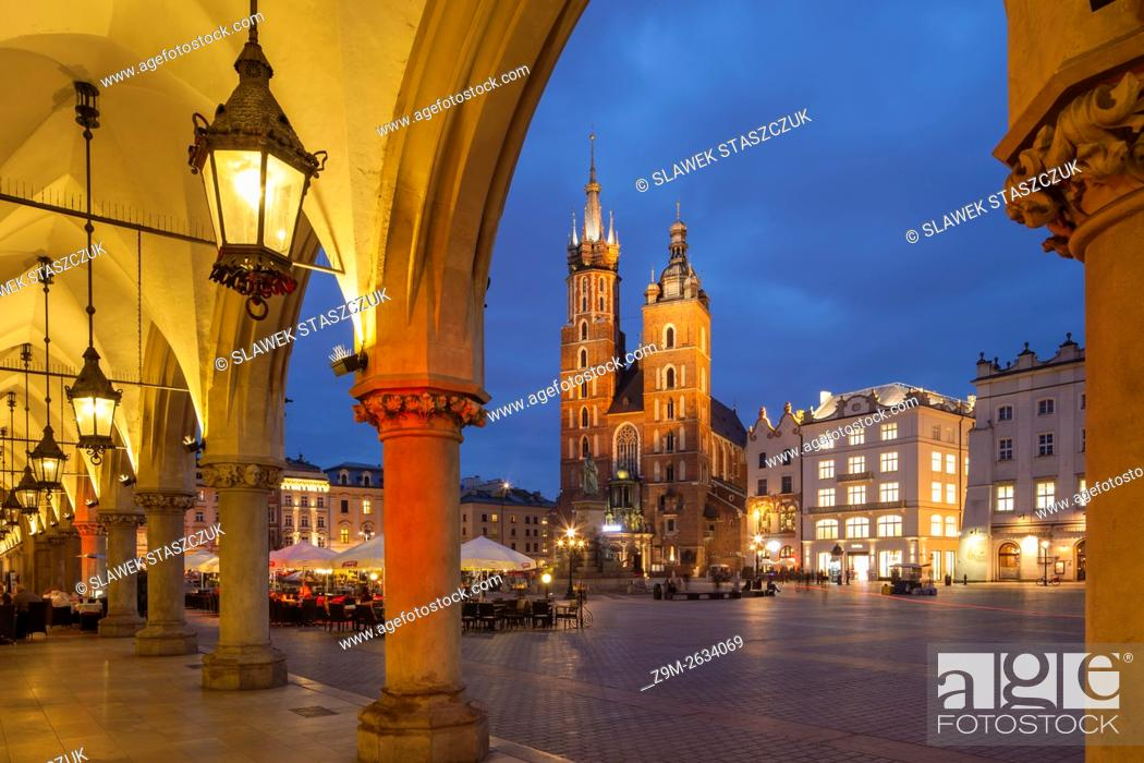 Imagen: Night falls at the Cloth Hall in Krakow old town, Poland. Looking towards St Mary's church. UNESCO world heritage site.