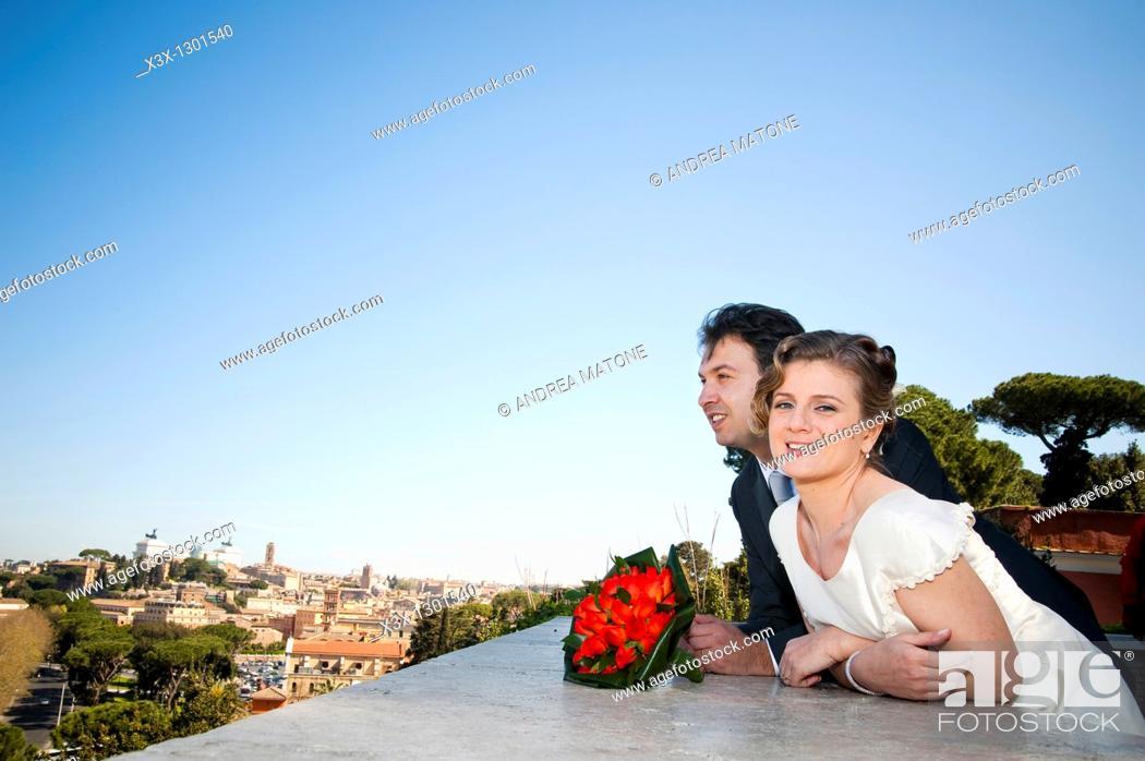 Stock Photo: Bride and groom overlooking Rome from the balcony of Giardino degli Aranci, Rome Italy.