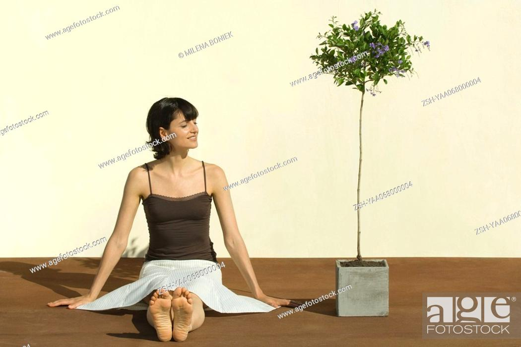 Stock Photo: Woman sitting on the ground next to potted tree, eyes closed, smiling.