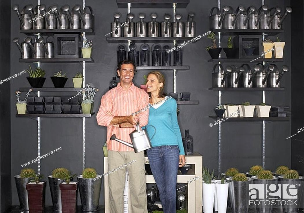 Stock Photo: Couple shopping in garden centre, man carrying watering can, indoors, portrait.