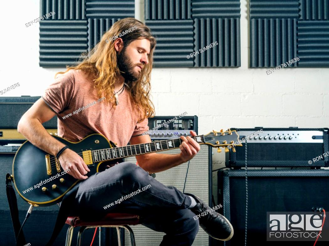 Imagen: Photo of an attractive man playing electric guitar in a recording studio.