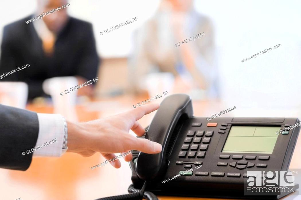 Stock Photo: Close-up of a businesswoman's hand reaching to a conference phone receiver.
