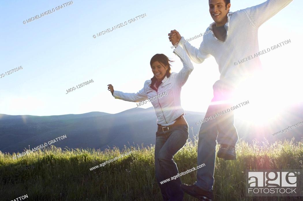 Stock Photo: Young couple running and jumping in mountain field.