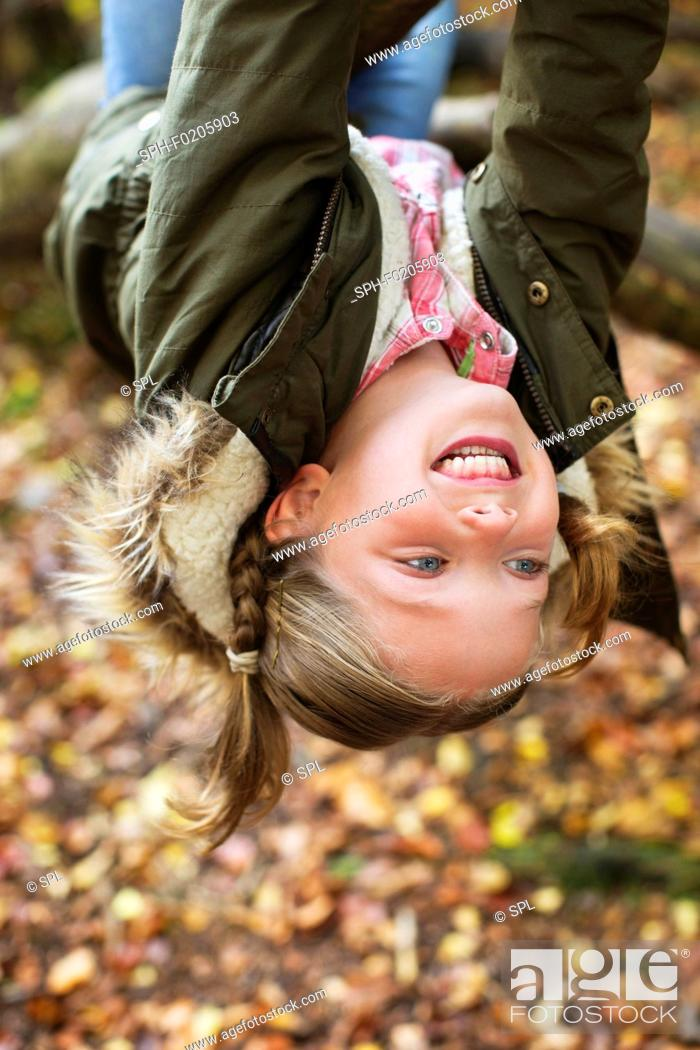 Stock Photo: Young girl hanging upside down.