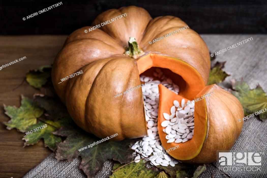 Imagen: pumpkin lying on a wooden table with viburnum and seeds.