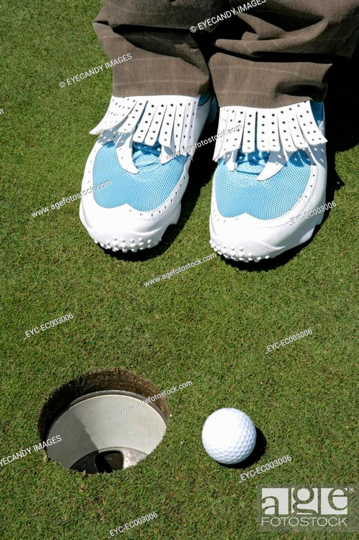 Stock Photo: View of a person standing near a golf hole.