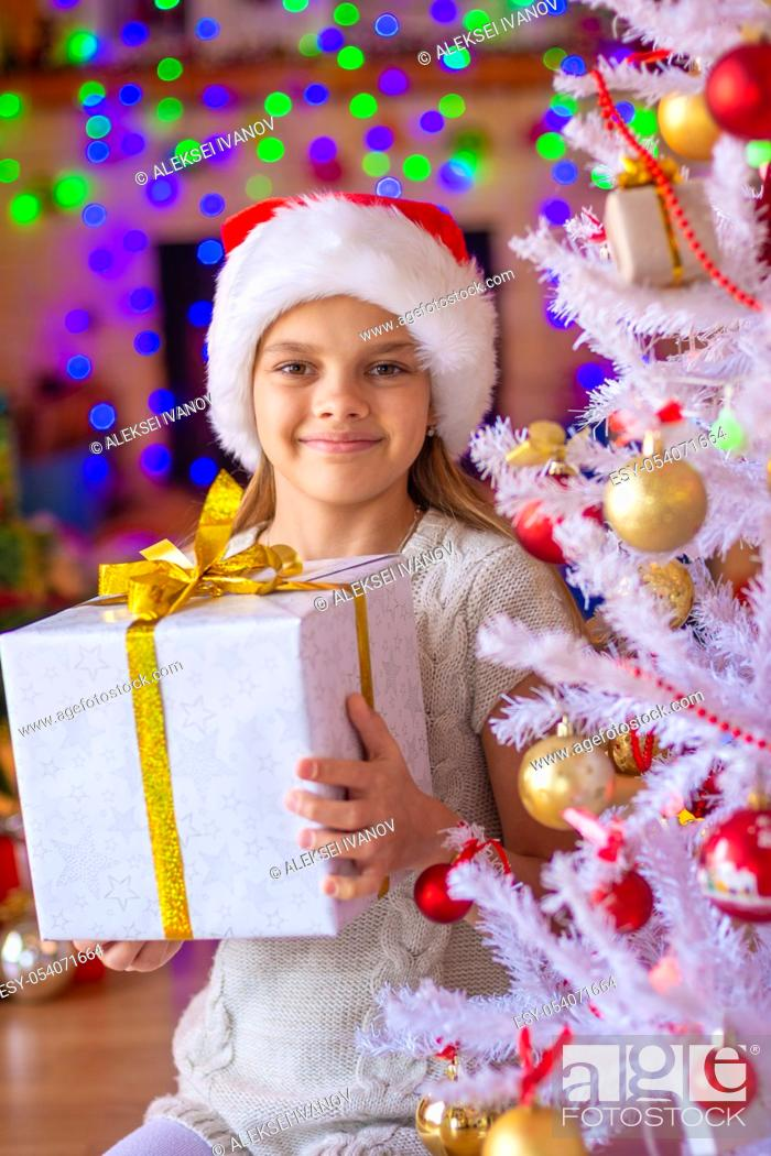 Stock Photo: Girl sitting by the Christmas tree with big gifts in her hands.