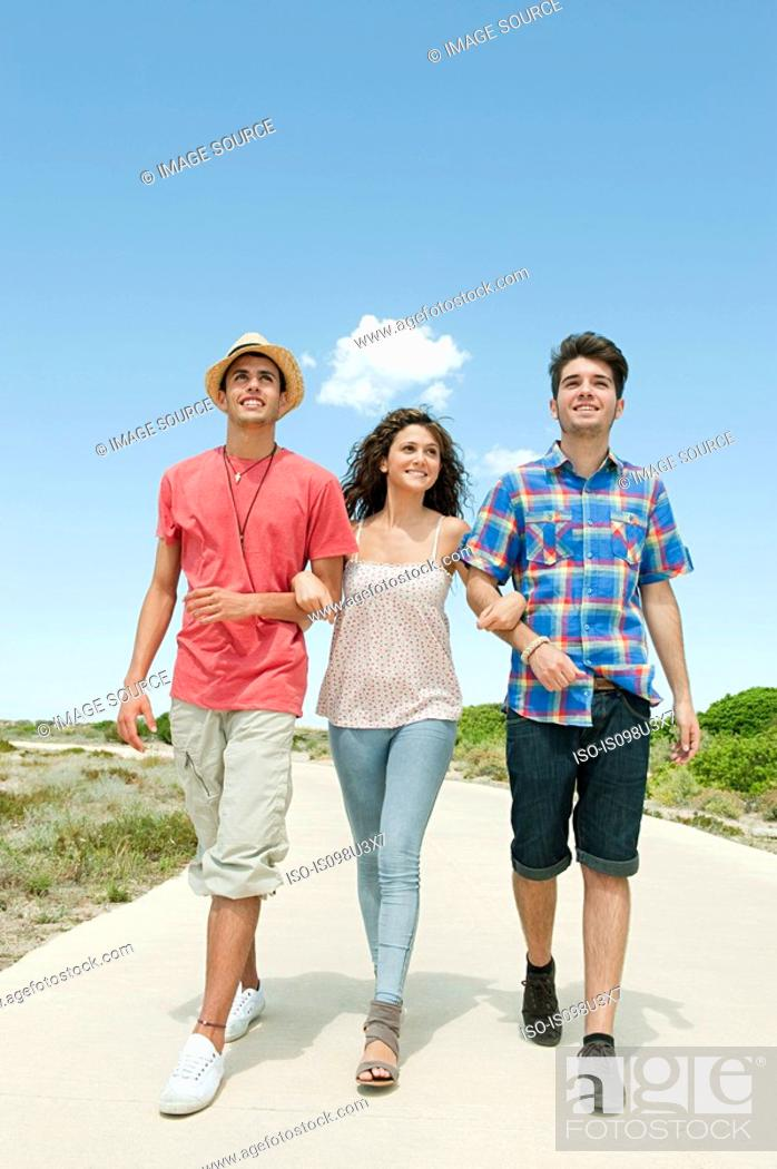 Stock Photo: Young friends walking down rural road.
