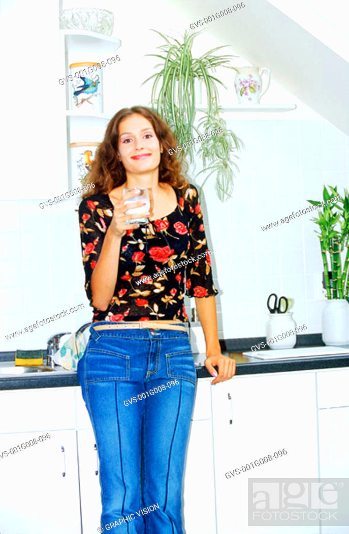 Stock Photo: Portrait of a young woman holding a glass of milk in the kitchen.