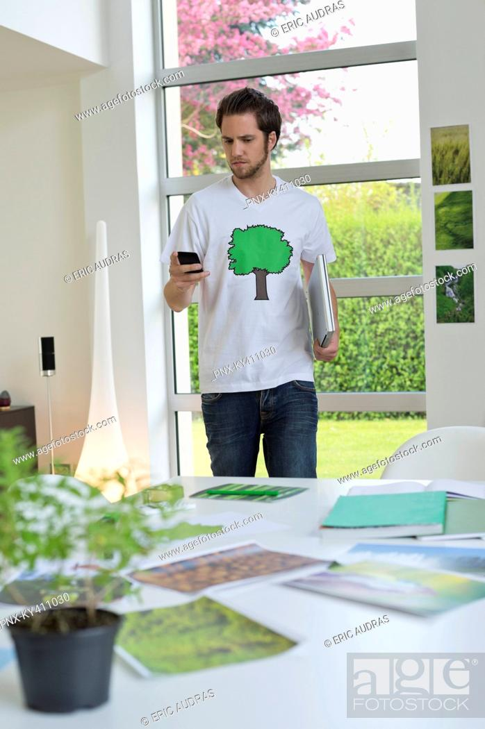 Stock Photo: Man using a mobile phone with environment related posters in front of him on a table.