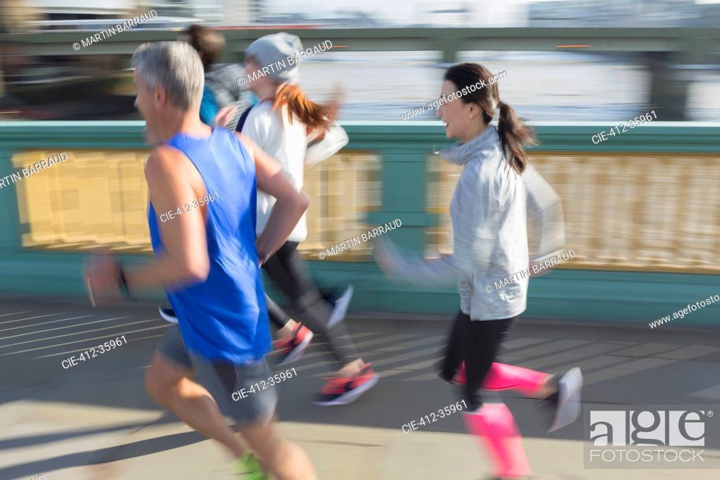 Stock Photo: Runners running on sunny urban bridge sidewalk.