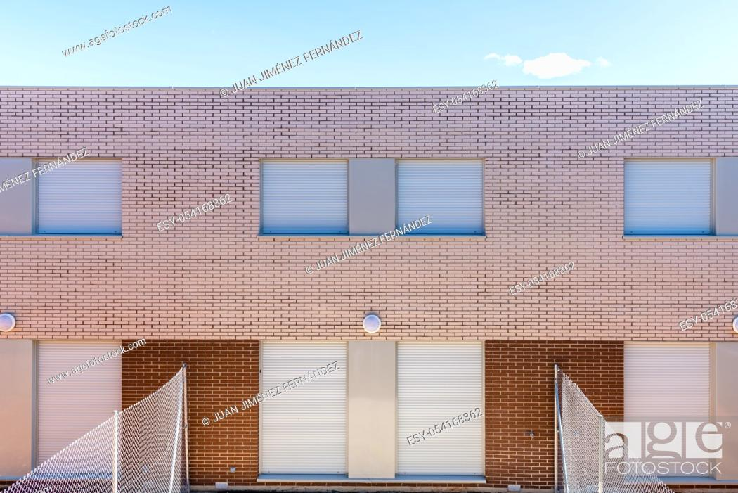 Stock Photo: Exterior view of modern semi-detached townhouses with brick facade. Sunny day.