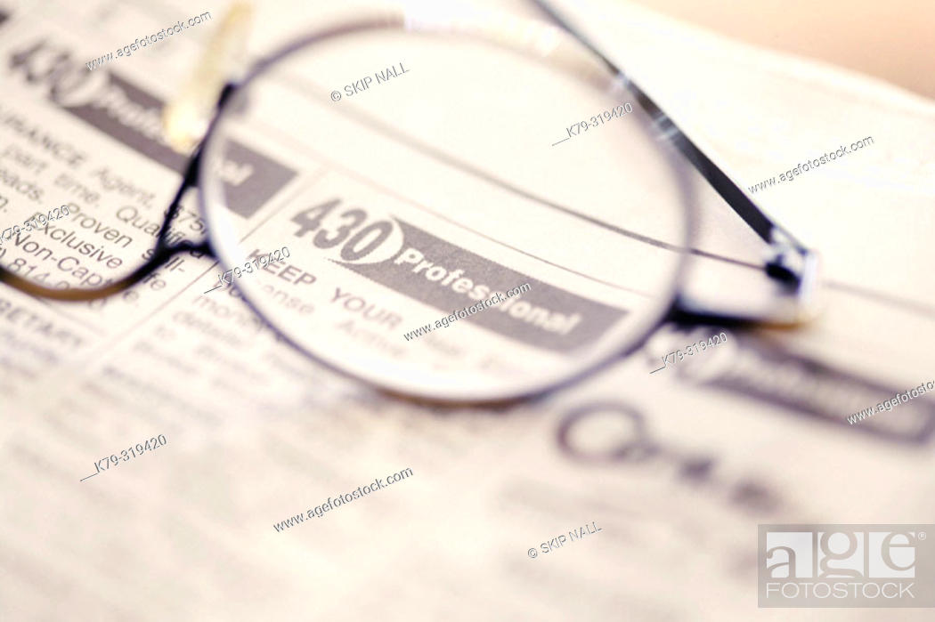 Stock Photo: Glasses laying on classified ads.