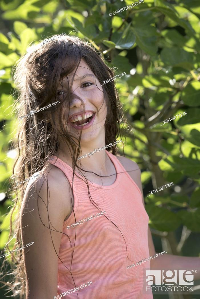 Photo de stock: Young girl in denim shorts and pink-orange tank top with wet hair posing in front of a fig tree, France.