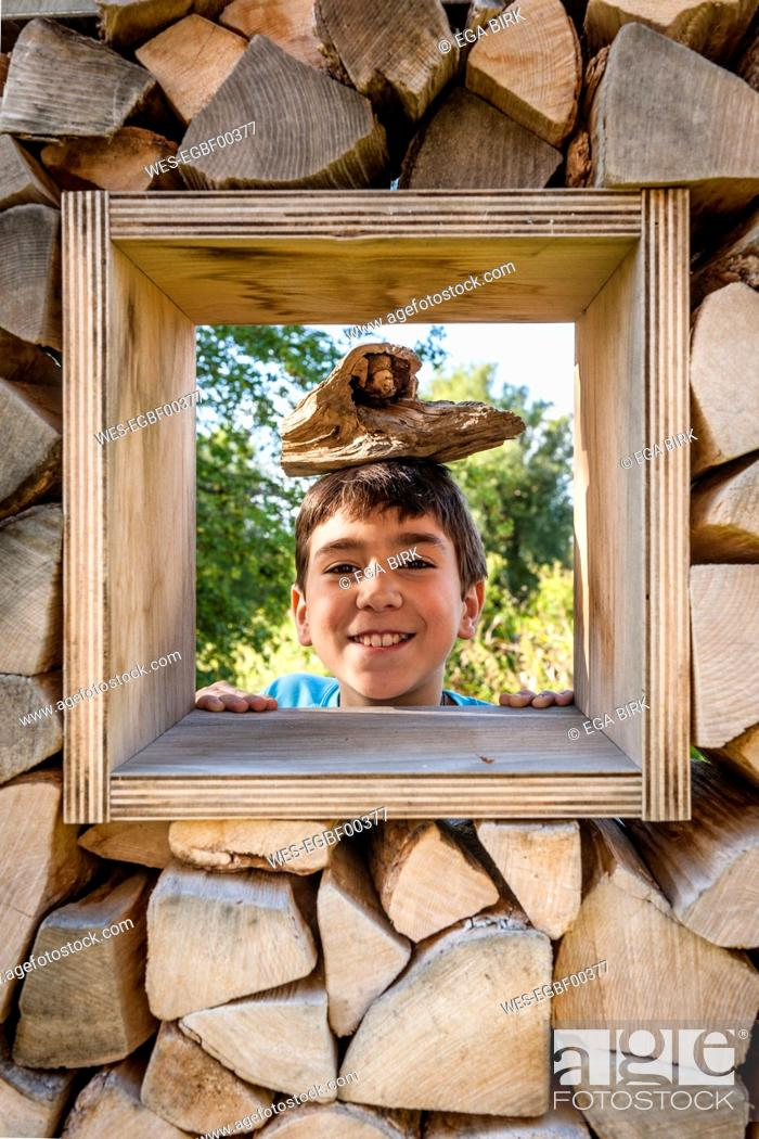 Stock Photo: Portrait of smiling boy looking through window in logpile.