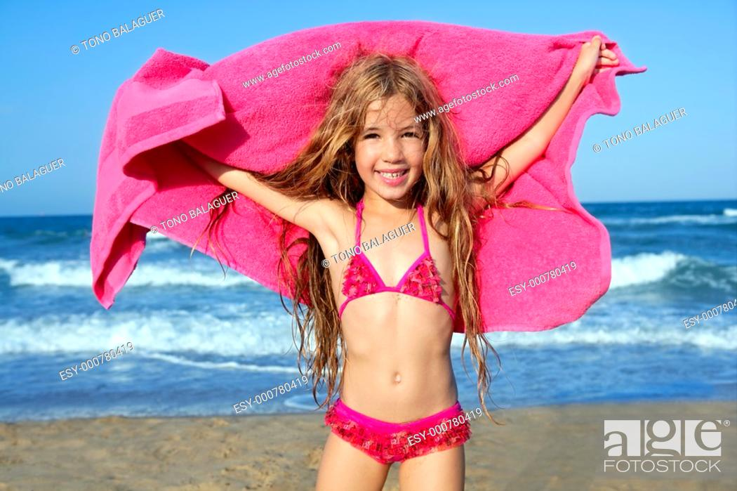 Photo de stock: Beach little girl playing pink towel and wind in blue sea.