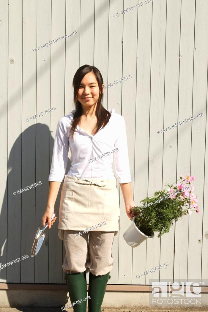 Stock Photo: Teenage girl 14-15 standing with shovel and potted plant, portrait.