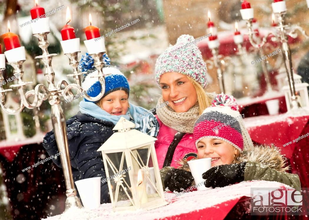 Stock Photo: Austria, Salzburg, Mother with children at christmas market, smiling.