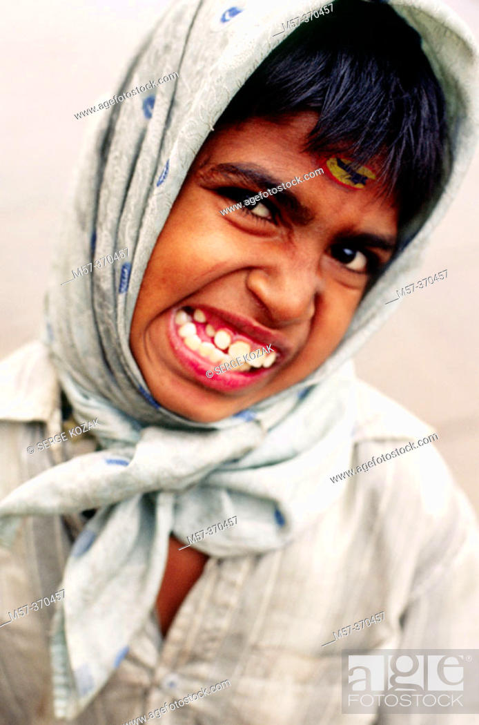 f72ec5d012 Stock Photo - Young Indian boy in a headscarf grinding his teeth and  pulling a face. Varanasi, India