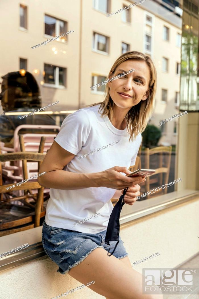 Stock Photo: Portrait of woman with smartphone and protective mask in her hand waiting in front of a coffee shop.