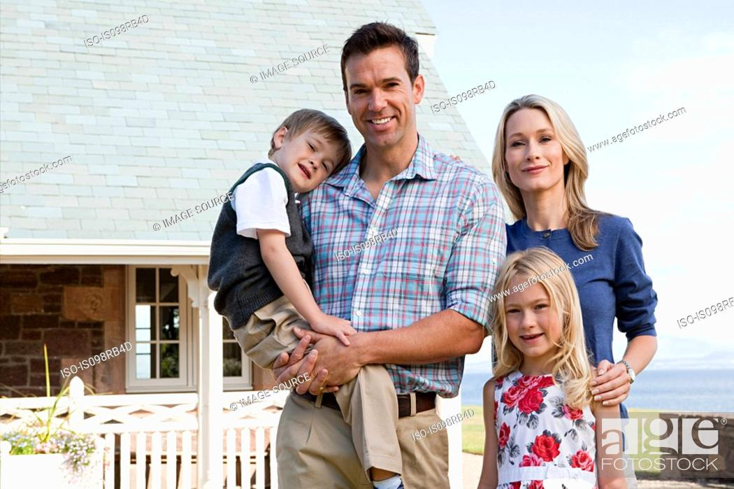 Stock Photo: Family outside holiday home.