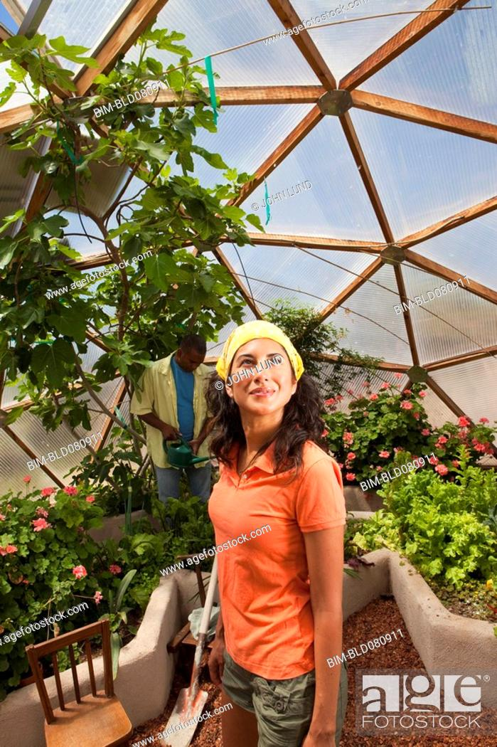 Stock Photo: Ecuadorian woman looking up in greenhouse.