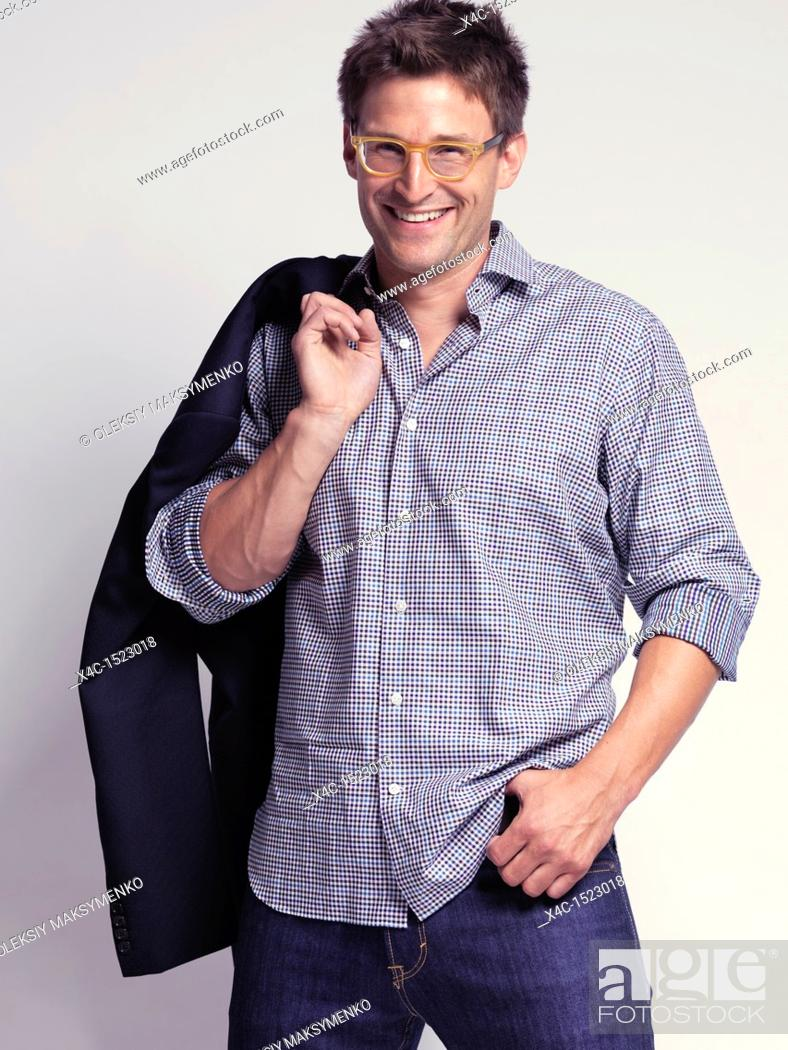 Stock Photo: Fashionably dressed smiling man in his thirties wearing jeans and a shirt, holding a jacket over his shoulder.