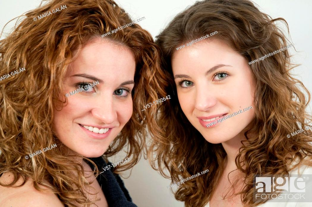 Stock Photo: Two young women smiling and looking at the camera. Close view.