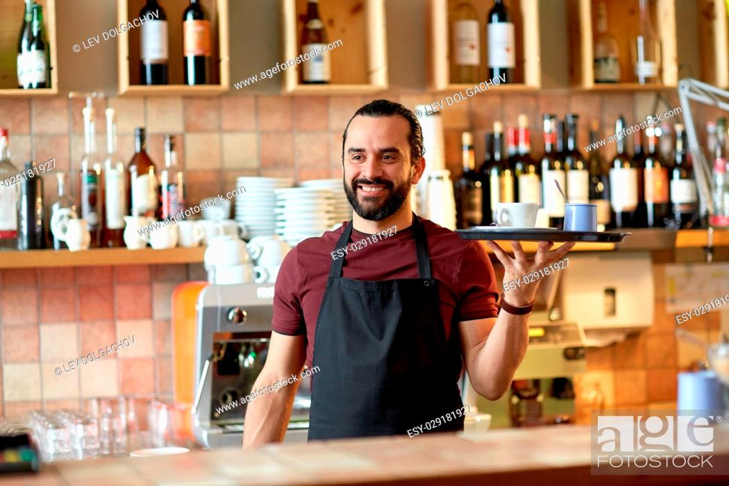 Stock Photo: small business, people and service concept - happy man or waiter in apron holding tray with coffee cup and sugar-bowl at bar.