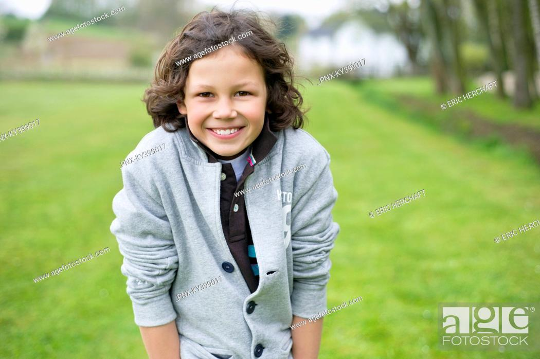 Stock Photo: Portrait of a boy smiling in a field.