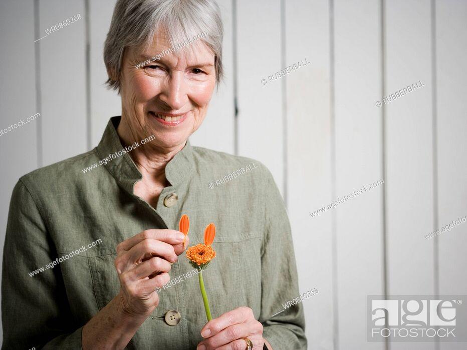 Stock Photo: Portrait of an elderly woman holding a flower.