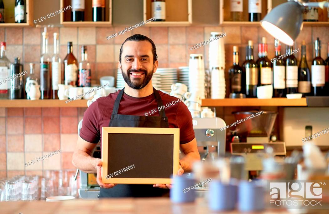Stock Photo: small business, people and service concept - happy man or waiter in apron with black chalkboard banner at bar or coffee shop.