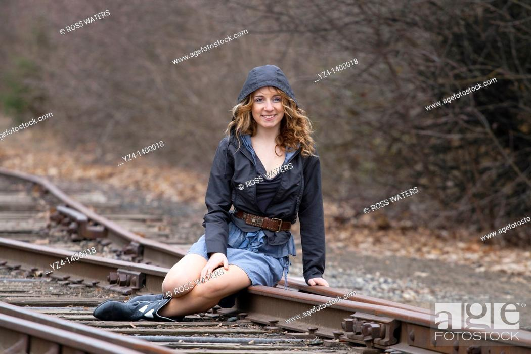 Stock Photo: A young woman sitting on train tracks.
