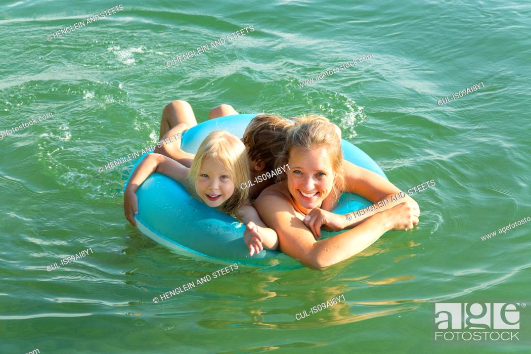 Stock Photo: Mother with daughter and son in inflatable ring, Lake Starnberg, Bavaria, Germany.