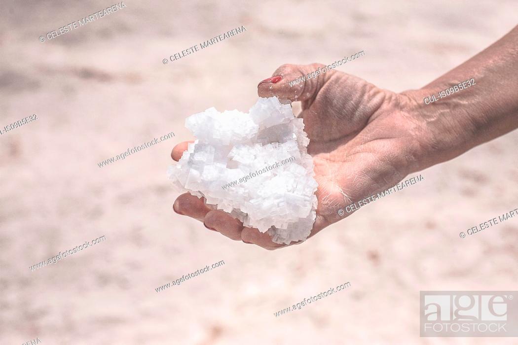 Stock Photo: Mature woman holding salt from salt flats, close-up, Jujuy, Salta Province, Argentina.